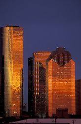 Stock photo of a Texas sunset reflected in the glazed facades of the downtown Houston skyline.