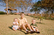 An older uncle with his two nephews sit on tropical grass in the family African garden in 1970. This amateur family souvenir portrait is a snapshot taken decades before the advent of the digital photograph, preserving the quality of a bygone era. The garden is in the African town of Blantyre in Malawi where this expatriate family lived. This decade is shown with the shorts sandals of seventies childhood.