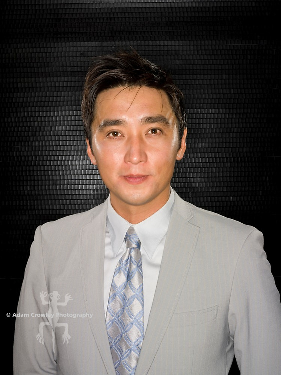 Asian man in grey suit and tie in front of black background