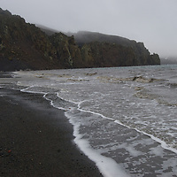 Waves wash onto a beach of black volcanic ash at Whaler's Bay on Deception Island, a huge caldera near  Antarctica that last erupted in 1969.
