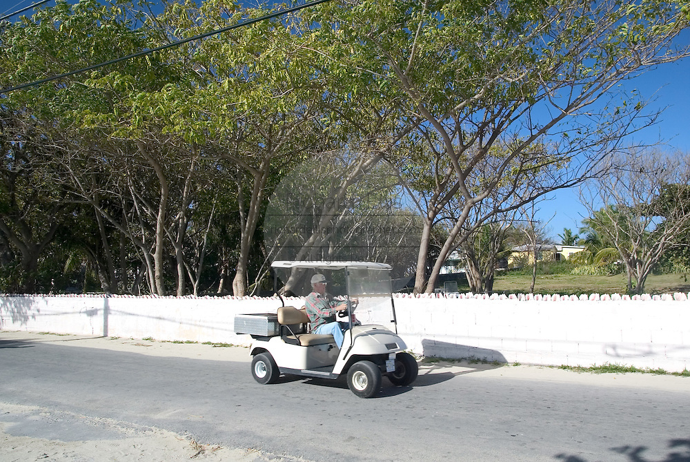 A tourist rides a golf cart along the King's Highway in Alice Town on the tiny Caribbean island of Bimini, Bahamas. Golf carts are the main form of transportation on the island.