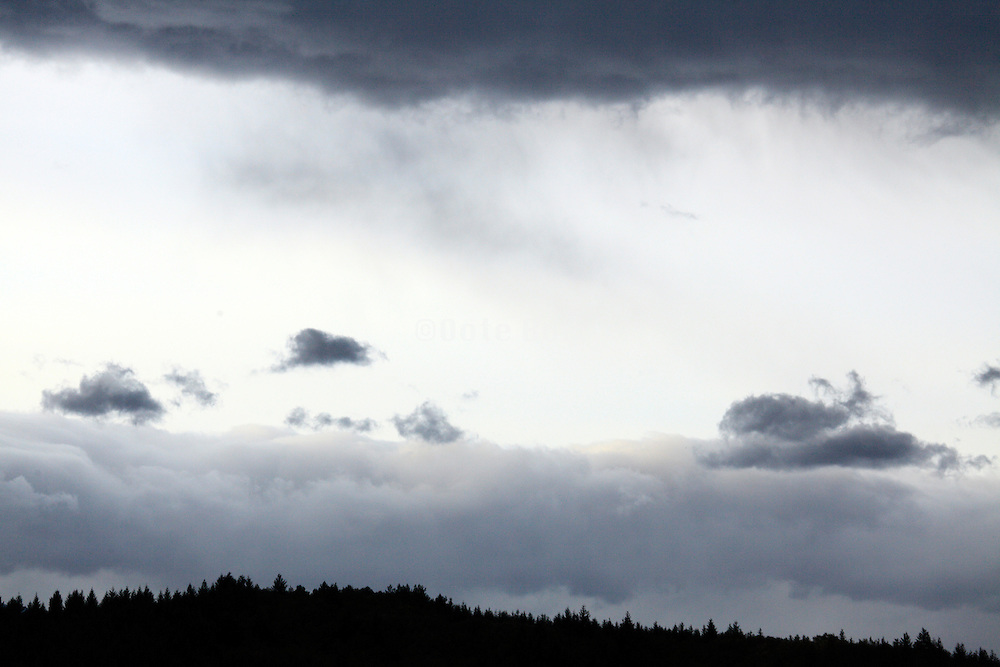wind swept cloud formations above a silhouetted hilly landscape