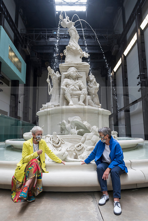 """© Licensed to London News Pictures. 24/07/2020. LONDON, UK. Maria Balshaw (L), Director Tate, and Frances Morris, Director Tate Modern, wearing facemasks pose next to """"Fons Americanus"""", 2019, by Kara Walker. Press preview ahead of the reopening of Tate Modern on 27 July after the easing of coronavirus pandemic lockdown restrictions by the UK government.  Visitors will need to book timed tickets online and follow one-way routes around the gallery space along with observing social distancing rules.  Photo credit: Stephen Chung/LNP"""