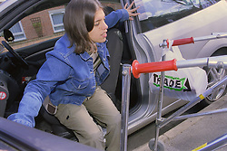 Teenage girl with physical disability getting out of car,