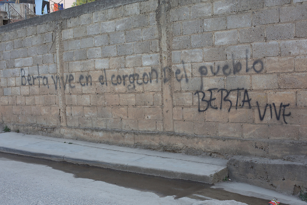 A street scene in Intibucá outside the city prison, the graffitti on the wall says 'Berta vive en el corazón del pueblo' (Berta lives in the heart of the people) and 'Berta Vive' )Berta Lives). Berta Cáceres campaigned and organised communities in Intibucá and other areas of Honduras to defend indigenous rights and territories before her assassination.