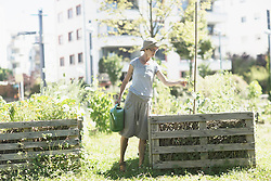 Mature woman watering plants in urban garden, Freiburg im Breisgau, Baden-Wuerttemberg, Germany