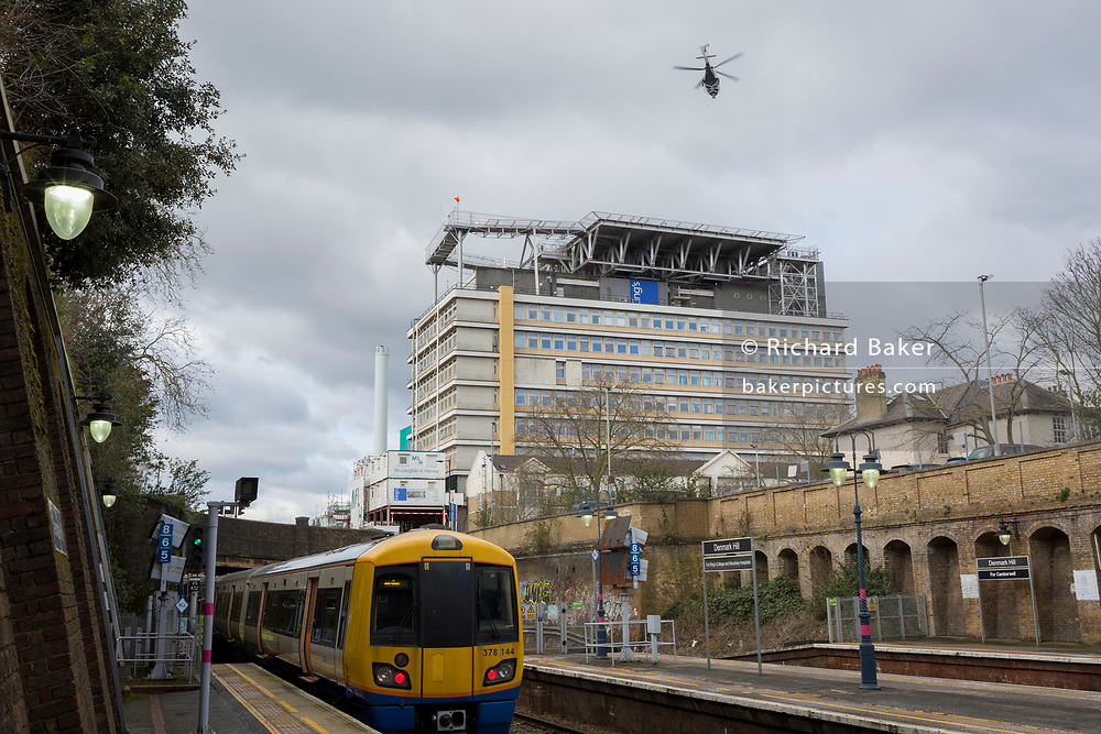 As a helicopter from an Air Ambulance service takes off into overcast skies from the helipad on the roof of Kings College Hospital Trust, a London Overground train leaves nearby Denmark Hill station, en-route towards Brixton and Clapham Junction, on 27th February 2020, in London, England.