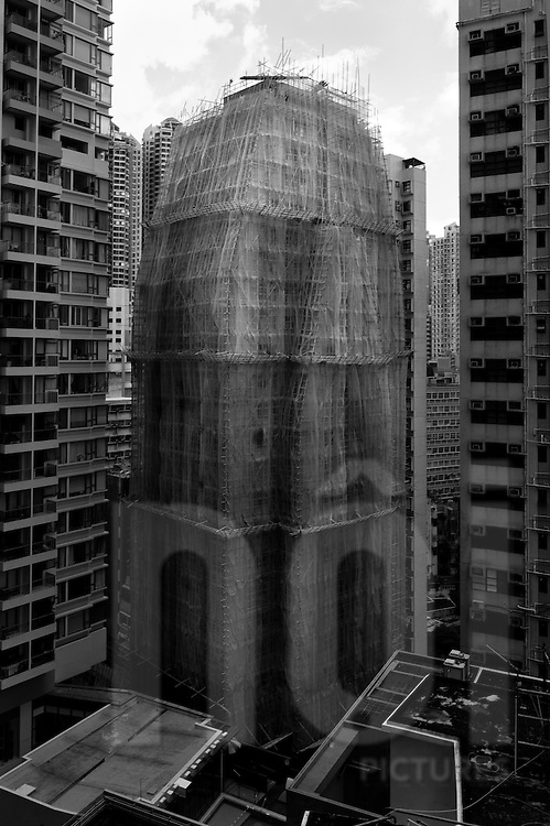 A Hong Kong high rise is covered with bamboo scaffolding during renovation, China, Asia