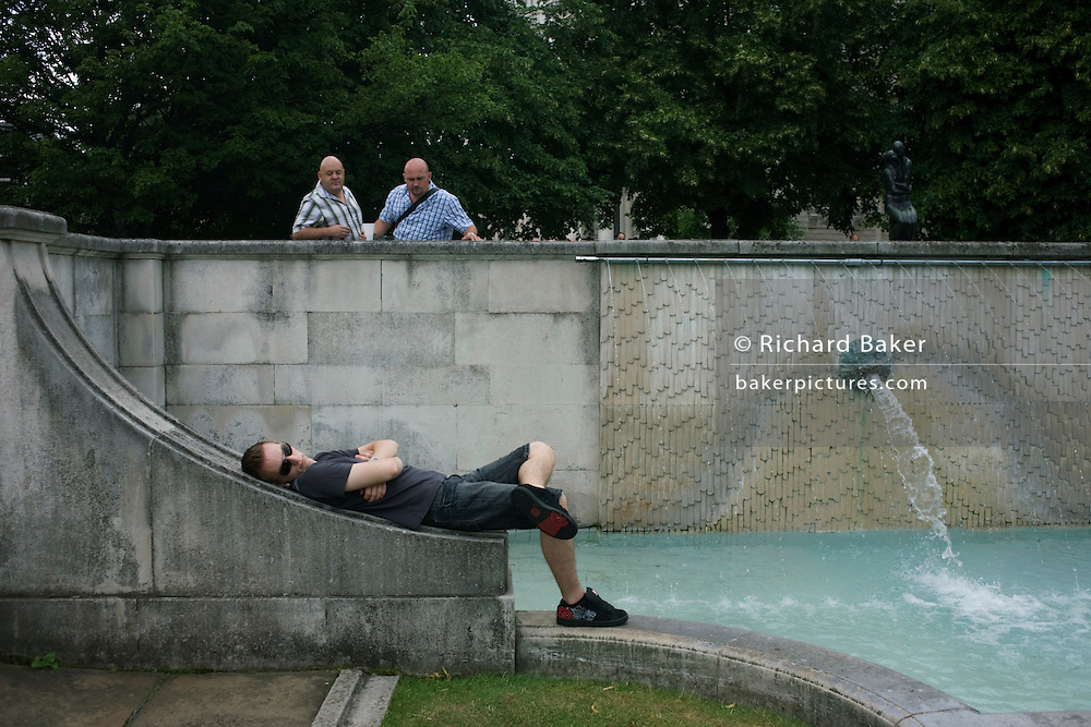 Two bald-headed men appear to show interest on a younger guy in public park near St. Paul's Cathedral.