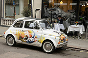 Fiat 500 car outside restaurant tables in Mayfair on 25th May 2021 in London, United Kingdom. As the coronavirus lockdown continues its process of easing restrictions, more and more people are coming to the West End as more businesses open.