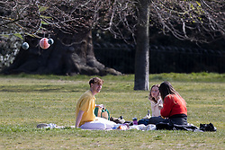 © Licensed to London News Pictures. 18/04/2021. London, UK. Members of the public relax and enjoy the sunny weather in Greenwich Park in South East London. Temperatures are expected to rise with highs of 16 degrees forecasted for parts of London and South East England this week . Photo credit: George Cracknell Wright/LNP