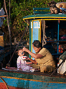 An old woman feeds a baby in one of the floating village communities on the great Tonlé Sap lake, Cambodia