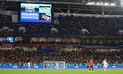 A big screen inside the stadium shows VAR in use during the game