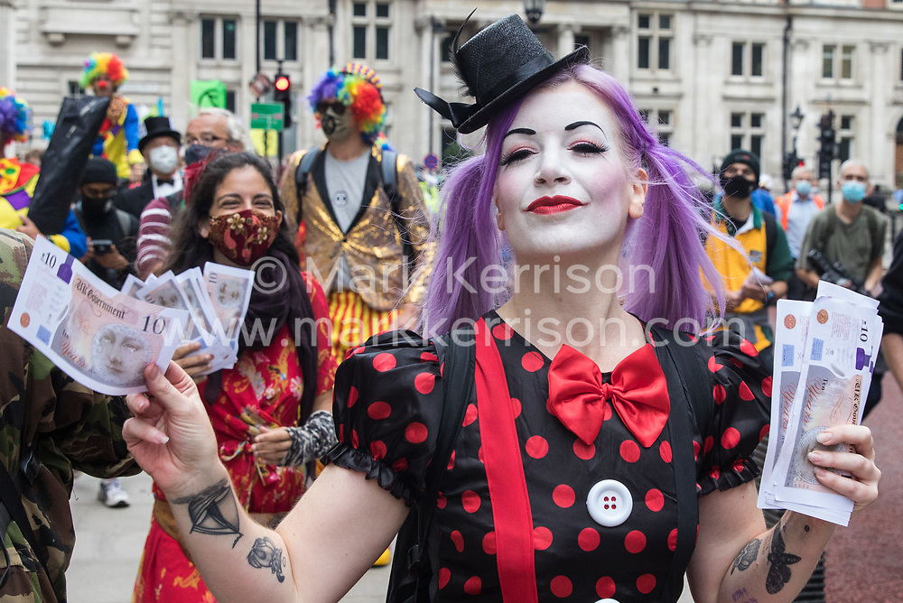 A troupe of clowns joins fellow climate activists from Extinction Rebellion attending a 'Carnival of Corruption' protest against the government's facilitation and funding of the fossil fuel industry on 3 September 2020 in London, United Kingdom. Extinction Rebellion activists are attending a series of September Rebellion protests around the UK to call on politicians to back the Climate and Ecological Emergency Bill (CEE Bill) which requires, among other measures, a serious plan to deal with the UK's share of emissions and to halt critical rises in global temperatures and for ordinary people to be involved in future environmental planning by means of a Citizens' Assembly.