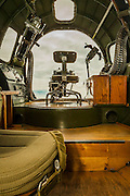 Bombardier's position in the nose of a B-17 bomber.  .50 caliber machine guns are on either side of his seat, with ammunition boxes to the right.  A moveable, remotely-controlled turret with two machine guns is directly below...