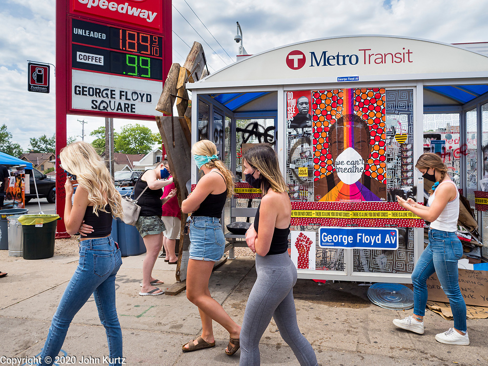 """12 JUNE 2020 - MINNEAPOLIS, MINNESOTA: People walk past a bus shelter turned into a part of the impromptu community memorial for George Floyd at the corner of 38th Street and Chicago Ave. in Minneapolis. The intersection is informally known as """"George Floyd Square"""" and is considered a """"police free zone."""" There are memorials to honor Black people killed by police and people providing free food at the intersection. Floyd, an unarmed Black man, was killed by Minneapolis police on May 25 when an officer kneeled on his neck for 8 minutes and 46 seconds. Floyd's death sparked weeks of ongoing protests and uprisings against police violence around the world.          PHOTO BY JACK KURTZ"""