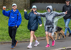 Licensed to London News Pictures. 23/05/2021. London, UK. Walkers doing the 15 mile Marsden March get caught in the rain in Wimbledon Village, South West London as weather forecasters predict yet more rain and wind until this Wednesday as the miserable May Spring weather continues. However, sun is on the way for the May Bank Holiday with temperatures expected to hit 21c by the end of the month. Photo credit: Alex Lentati/LNP