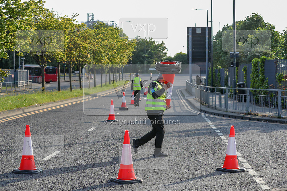 Testing Centre personnel for COVID-19 at a drive-through testing centre in a car park are seen collecting traffic control cones at O2 Testing centre in Greenwich, London, Monday, May 4, 2020. <br /> The UK continues in lockdown to help curb the spread of the coronavirus, which has impacted on nations around the globe imposing self-isolation and exercising social distancing when people move from their homes. (Photo/ Vudi Xhymshiti)