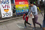 The day after UK Prime Minister Boris Johnson addressed the nation with his roadmap for the coming weeks and months during the Coronavirus pandemic lockdown, a family walk past banners supporting and thanking NHS (National Health Service) key workers, outside the Maudsley Hospital that specialises in mental health services and is opposite King's College Hospital (one of the capital's major trauma centres and a site for Covid patients, on 11th May 2020, in London, England.