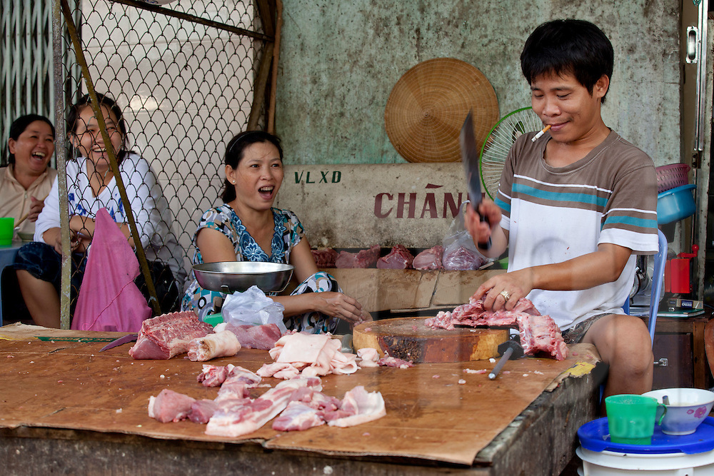 A vietnamese butcher is holding a big knife to slice pork for customer. Women behind him look surprised by his action. Go Dau, Tay Ninh province, Vietnam,Asia.