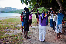 """Sunrise yoga practitioners shout """"Harambe!"""" seven times and hold hands in a circle to conclude the morning Kwanzaa celebration.  Harambe means """"Let's all pull together""""."""