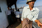 """17 JUNE 2013 - YANGON, MYANMAR: A Burmese man going to Dala on the Yangon-Dala Ferry. The ferry to Dala opposite Yangon on the Yangon River is the main form of transportation across the river. Every day the ferry moves tens of thousands of people across the river. Many working class Burmese live in Dala and work in Yangon. The ferry is also popular with tourists who want to experience the """"real"""" Myanmar. The rides takes about 15 minutes. Burmese pay about the equivalent of .06¢ US for a ticket.  Foreigners pay about the equivalent of about $4.50 US for the same ticket.    PHOTO BY JACK KURTZ"""