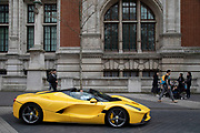 Yellow Ferrari supercar passes in South Kensington, one of the most exclusive areas in central London, England, United Kingdom. In a selected few boroughs of West London, wealth has changed over the last couple of decades. Traditionally wealthy parts of town, have developed into new affluent playgrounds of the super rich. With influxes of foreign money in particular from the Middle-East. The UK capital is home to more multimillionaires than any other city in the world according to recent figures. Boasting a staggering 4,224 ultra-high net worth residents - people with a net worth of more than $30million, or £19.2million.