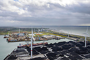 Nederland, Zeeland, Borssele, 23-10-2013; energielandschap, haven bij Borssele. Opslag van steenkool, windmolens aan de dijk van de Westerschelde met o.a. het oranje gebouw van COVRA (Centrale Organisatie Voor Radioactief Afval) , kerncentrale Borssele middenboven. <br /> Port and  industrial area with storage of coal and COVRA, a company that handles the storage of radioactive waste. In the back nuclear plant Borssele (m).<br /> luchtfoto (toeslag op standaard tarieven);<br /> aerial photo (additional fee required);<br /> copyright foto/photo Siebe Swart.).<br /> luchtfoto (toeslag op standaard tarieven);<br /> aerial photo (additional fee required);<br /> copyright foto/photo Siebe Swart.