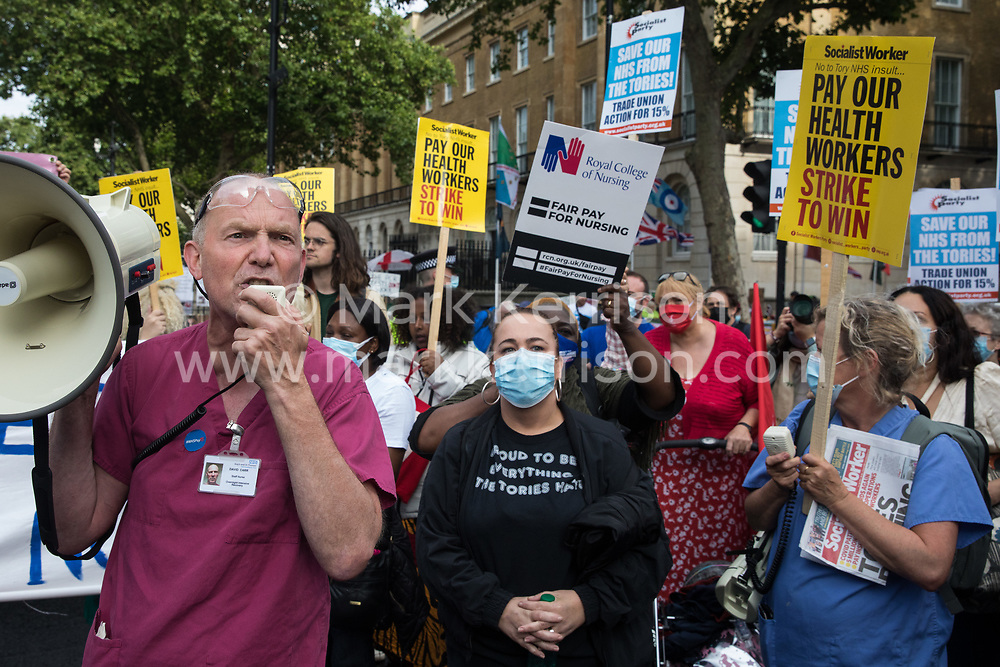 Staff nurse David Carr addresses NHS staff who marched from St Thomas' Hospital and UCH to Downing Street to protest against the NHS Pay Review Body's recommendation of a 3% pay rise for NHS staff in England on 30th July 2021 in London, United Kingdom. The protest march was supported by Unite the union, which has called on incoming NHS England Chief Executive Amanda Pritchard to ensure that a NHS pay rise comes from new Treasury funds rather than existing NHS budgets and which is shortly expected to put a consultative ballot for industrial action to its members.