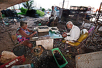 Palafitas or Stilt dwellers living and fishing on the river cleaning sorting mussels Recife in Northeastern Brazil.