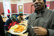 A man with his lunch at Slough Homeless our concern (SHOC) A local homeless charity helping the homeless and vulnerable in Slough. Berkshire, UK.