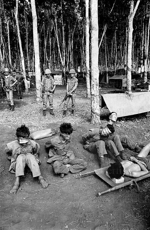 Injured and blind-folded North Vietnamese army - Viet Cong prisoners captured by the South Vietnam army near Xuan Loc, Vietnam, 1975. Xuan Loc was the last major battle of the Vietnam War fought between 9th and 21st April 1975. Photographed by  Terry Fincher. Contact thefincherfiles@btinternet.com for publication fees and permissions.