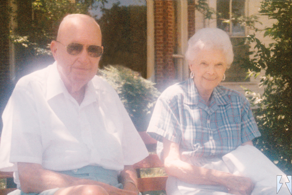 A happy couple in their 80's sitting on a bench dressed for the nice spring day in Austin Texas.