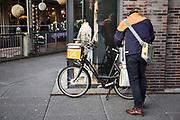Nederland, the netherlands, Nijmegen, 18-12-2019 Een postbode bezorgt de post op de fiets rijdt in de stad . De Postfiets, postbike,  moet wel zelf betaald worden . Foto: Flip Franssen