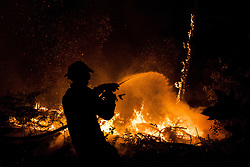 June 19, 2017 - Leiria, Portugal - A fire fighter douses flames with water in the Pedrogao Grande municipality. A raging forest fire in central Portugal killed at least 62 people as they desperately tried to flee, charring cars and trucks as it swept over roads. The disaster, the worst tragedy Portugal has experienced in decades shook the nation. (Credit Image: © Atlantico Press via ZUMA Wire)
