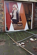 Hoardings showing as aspirational future near Bristol docks. A young, prosperous woman sits holding a mug of coffee on a street cafe and a fallen fence lies on the cobbled ground. The landscape is bleak, the remains of Victorian and early 20th century warehouses and harbour buildings that are now derelict and partially-demolished which are now due to be removed from the city's history, to be replaced by regenerated harbour view flats and apartments - homes for the wealthy middle-classes. The developer claims they are bringing the harbour area back to life but the days of tall ships importing trade from around the world (including slaves in the 18th century).