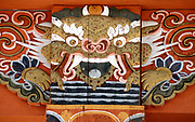 Representation of a dragon painted on wood in traditional Bhutanese style at the top of a concrete column in a new building. This emulates the tradition of painting timbers in traditional wood-built houses.  The dragon is the Bhutanese national symbol, Druk, the thunder dragon. Paro, Druk Yul, Kingdom of Bhutan. 10 November 2007.