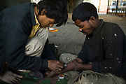 Homeless addicts prepare and inject heroin under a flyover, New Delhi, India
