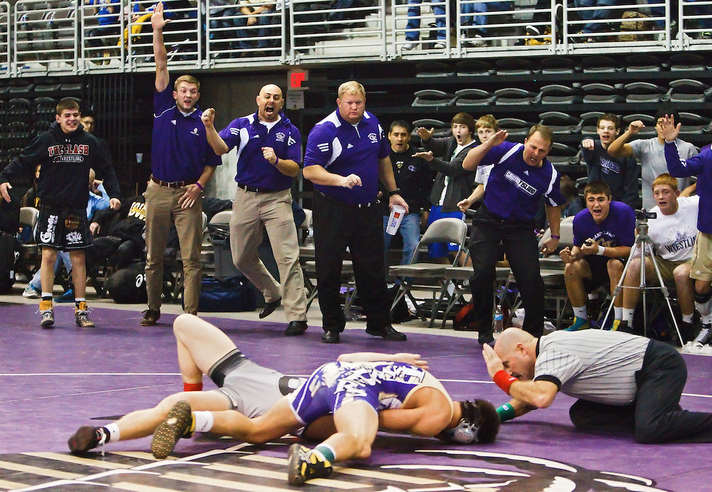Grand Island Senior High's bench erupts, including coaches, from left, Nate Westerby, head coach Mike Schadwinkel, assistant coaches Jeff Westerby and Rob Riedy, as Trey Trujillo pins Omaha Burke's Jacob Wilcoxen at 126 pounds, clinching both the dual and the title during the Flatwater Fracas Saturday at the Heartland Events Center. Trujillo pinned Wilcoxen in 5:53. (Independent/Matt Dixon)