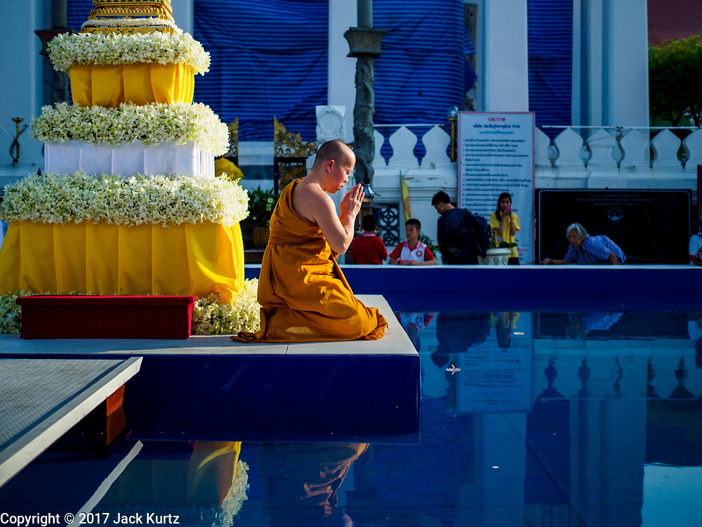 """03 NOVEMBER 2017 - BANGKOK, THAILAND: A monk at Wat Prayurawongsawat on the Thonburi side of the Chao Phraya River, prays during Loi Krathong. Loi Krathong is translated as """"to float (Loi) a basket (Krathong)"""", and comes from the tradition of making krathong or buoyant, decorated baskets, which are then floated on a river to make merit. On the night of the full moon of the 12th lunar month (usually November), Thais launch their krathong on a river, canal or a pond, making a wish as they do so. Loi Krathong is also celebrated in other Theravada Buddhist countries like Myanmar, where it is called the Tazaungdaing Festival, and Cambodia, where it is called Bon Om Tuk.     PHOTO BY JACK KURTZ"""