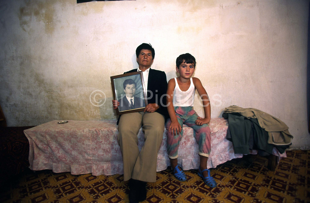 Selman Brahim has been living as a man for 40 years after the family's eldest son died. In the Albanian tradition of the Avowed Virgin ('Virgjineshe' or 'Sworn Virgins'), authorised by the Kanun of Lek (an ancient system of laws) she/he now leads the family as a man. She is seen here with her sister's grandchild and a picture of her as a younger person. Lepurush Village near Skhoder, Northern Albania
