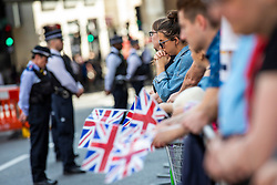 © Licensed to London News Pictures. 03/06/2018. London, UK. A woman holds her hands together during a minute's silence by London Bridge to mark the first anniversary of the London Bridge and Borough Market terror attack. Photo credit: Rob Pinney/LNP