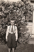 A young boy posing in the garden for a photograph
