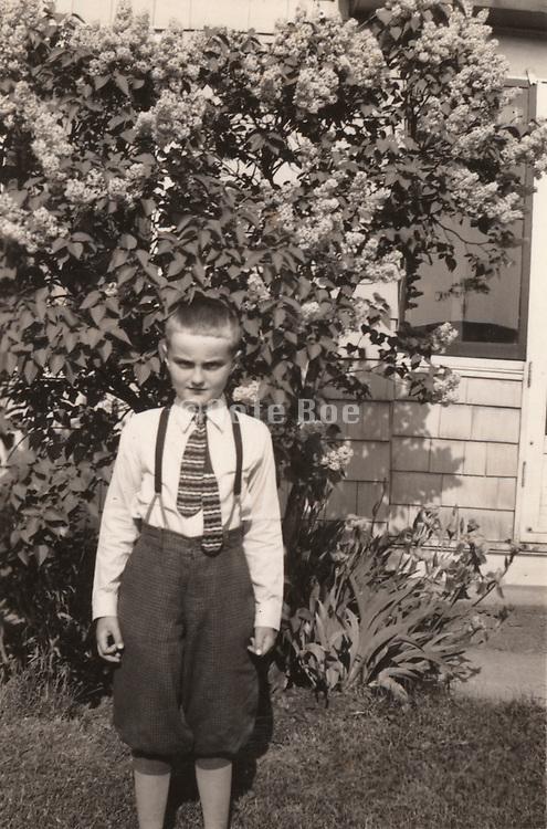A young boy posing in the garden for a photograph