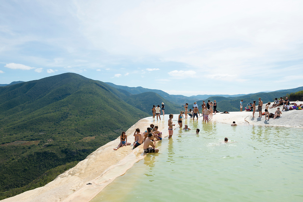 Tourists enjoy the water and dramatic scenery at Hierve el Agua in Oaxaca State, Mexico. The rock formation is created by fresh water springs, whose water is over-saturated with calcium carbonate and other minerals.