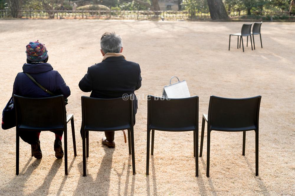 Elderly couple sitting outside in a garden