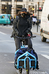 © Licensed to London News Pictures. 16/03/2020. London, UK. A woman wearing a face mask on a bicycle on Regent Street. 35 coronavirus victims have died and 1,372 have tested positive for the virus in the UK as of 9am on Sunday, 15 March 2020. Photo credit: Dinendra Haria/LNP