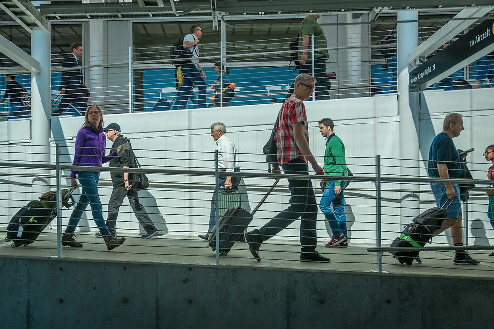 Arriving and departing travelers navigate passenger ramps at SeaTac International Airport.