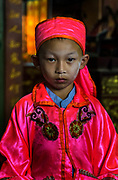 A young male performer of Lao Gheg Lao Cung (老玉楼春) chinese opera troupe helps prepare for an evening performance to family and friends at the Chao Por Lak Muang Shrine, Chinatown, Bangkok