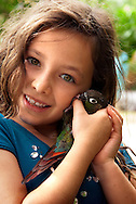 Smiling 8-year-old girl holding a bird – a green cheeked conure, the family pet.